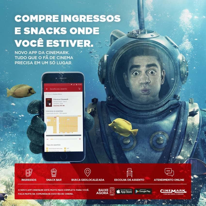 Marcelo Adnet no fundo do mar com um celular na mão divulgando novo app da Rede Cinemark para compra de ingressos, combos e vantagens exclusivas